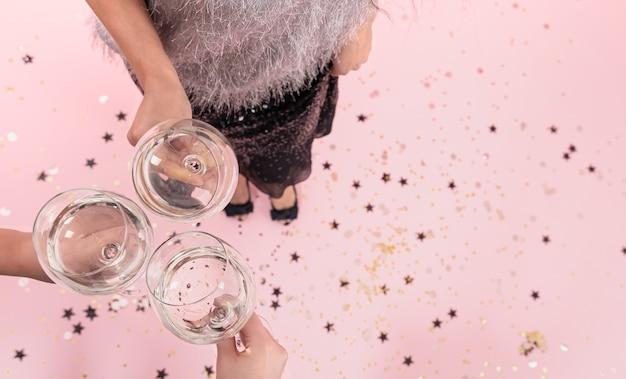 Verres à champagne dans les mains des filles lors d'une fête sur fond rose, espace de copie.