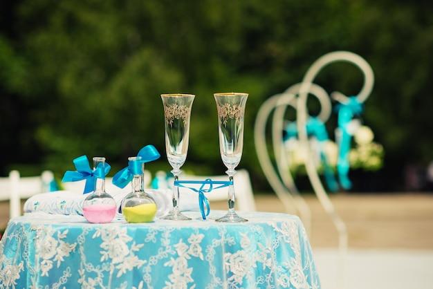 Verres de champagne et deux bouteilles de sable coloré.