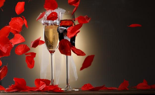 Verres de champagne élégants pour les mariés avec des pétales de rose