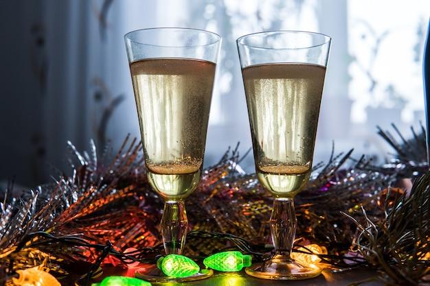 Verres à champagne sur fond de guirlande. fond de la saint-valentin. la célébration de noël et du nouvel an des couples amoureux
