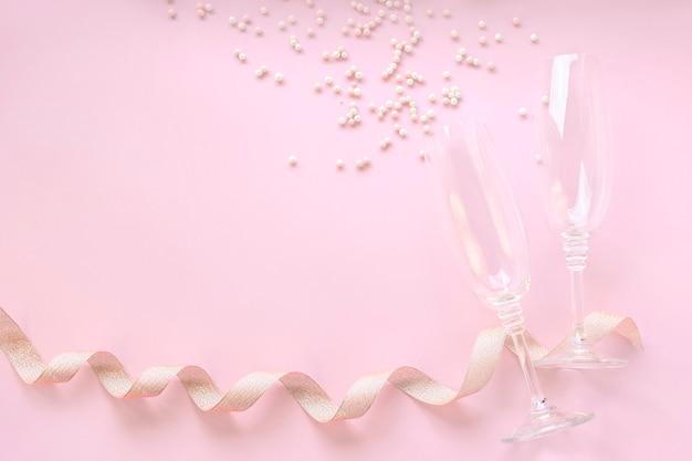 Verres à champagne avec perles blanches dispersées et ruban doré.