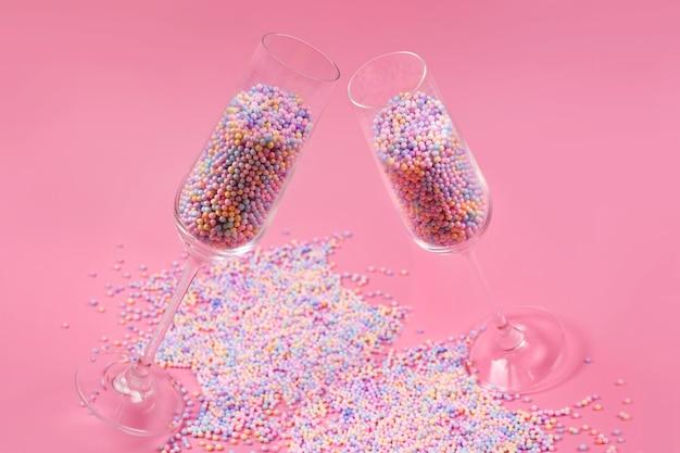 Verres à champagne remplis de boules de sucre colorées sur rose