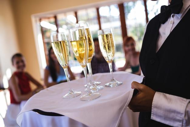 Verres de champagne serveuse sur plateau au restaurant