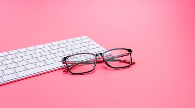 Verres et claviers d'ordinateur sur rose