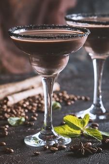 Verres de cocktail café crème ou martini au chocolat sur fond noir