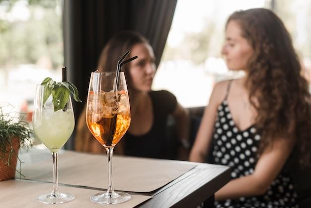 Verres à cocktail devant deux amies