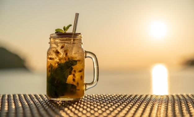 Verres à cocktail de fruits de la passion de glace avec des pailles sur la table en bois au coucher du soleil sur la mer.