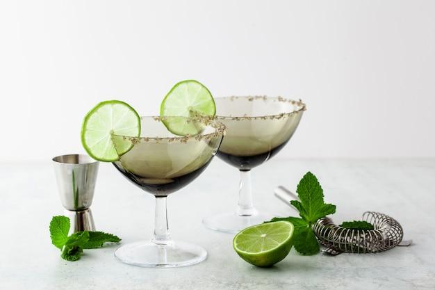 Verres à cocktail margarita vides sur une table avec accessoires de bar