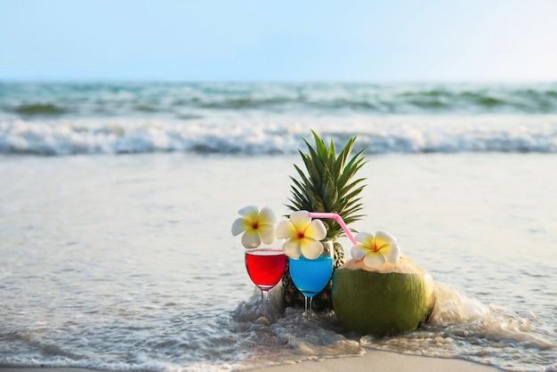 Verres à cocktail à la noix de coco et à l'ananas sur une plage de sable fin - fruits et boisson à la plage de la mer