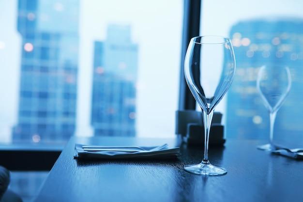 Verres à cocktail sur le rebord de la fenêtre par le verre d'un grand immeuble