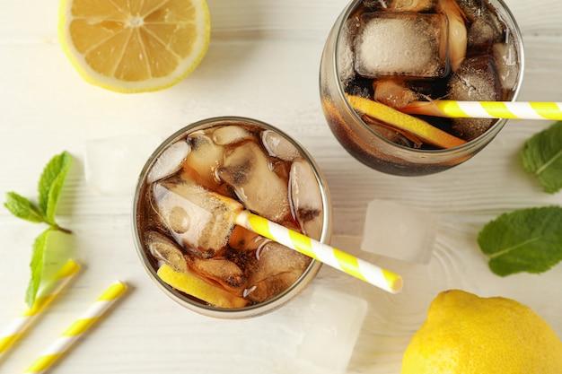 Verres avec cola froid et agrumes sur fond de bois blanc