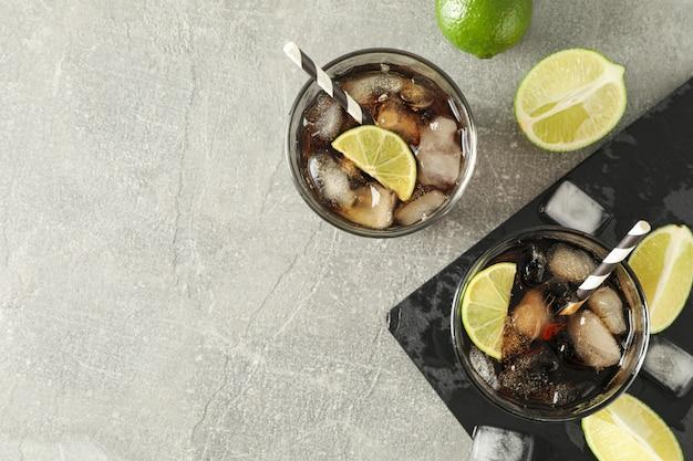 Verres avec cola froid et agrumes sur table grise, vue du dessus