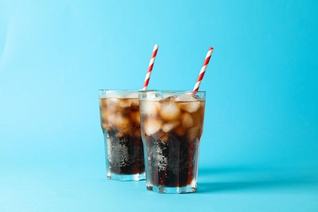 Verres à cola froid et tubule sur fond bleu, espace pour le texte