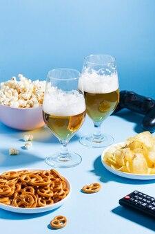 Verres de collations à la bière légère sur fond bleu avec une télécommande de la télévision un joystick