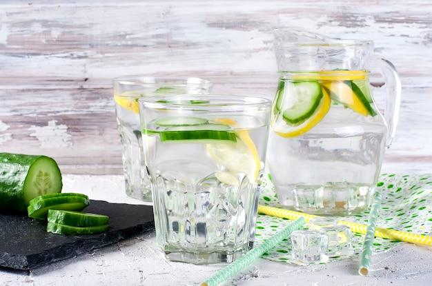 Verres avec concombre bio frais désintoxication, eau de menthe citronnelle sur tableau blanc