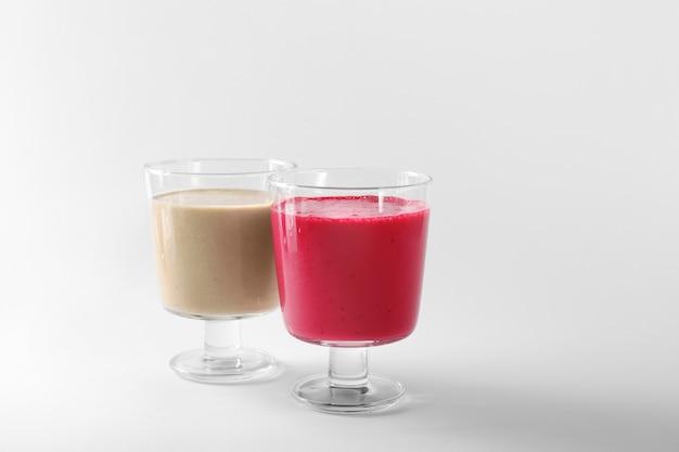 Verres avec différents smoothies sur blanc