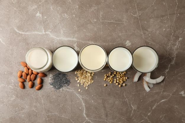 Verres avec différents types de lait sur brun, vue de dessus. fermer