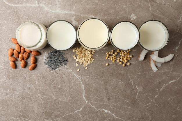 Verres avec différents types de lait sur table marron, vue de dessus. fermer