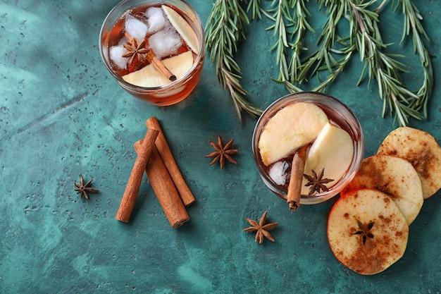 Verres avec du cidre de pomme et de la cannelle sur la table