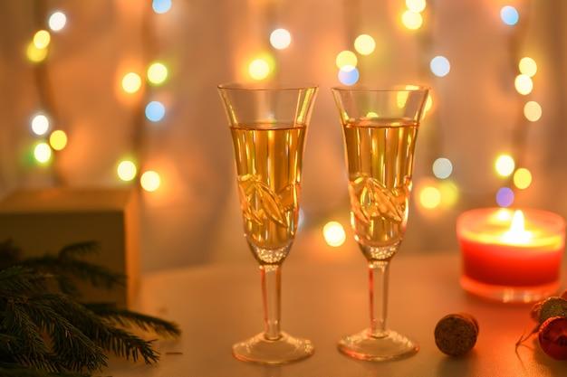 Verres du nouvel an sur fond de bougie allumée, coffret cadeau et guirlande lumineuse aux couleurs chaudes.