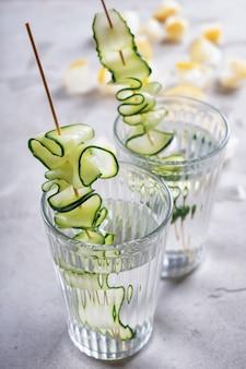 Verres d'eau de concombre frais sur table grise