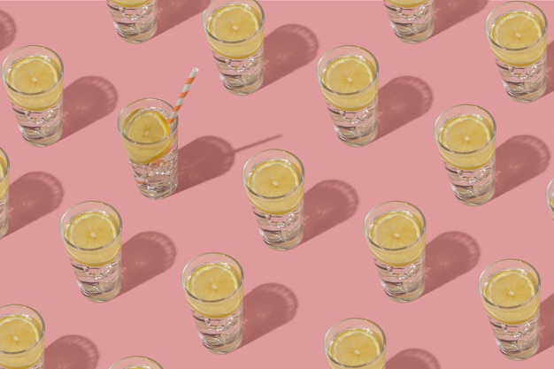 Verres d'eau froide avec glace et citron motif répété sur un fond rose.