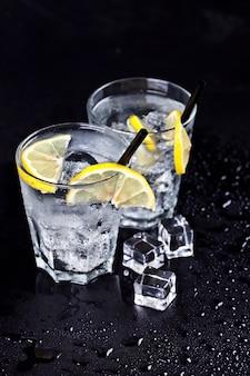 Verres avec de l'eau gazeuse fraîche et froide avec des glaçons et des tranches de citron