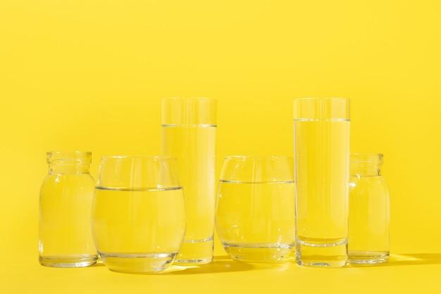 Verres avec de l'eau propre de différentes formes sur jaune.