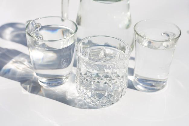 Verres avec de l'eau sur une surface blanche