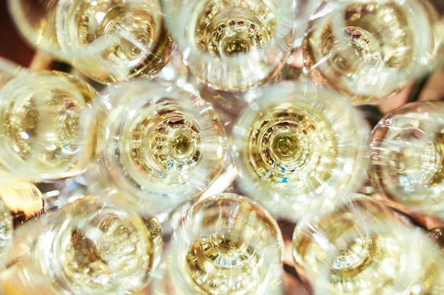 Verres élégants avec du champagne debout dans une rangée sur la table de service pendant la fête ou la célébration