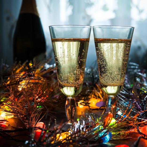Verres sur fond de guirlande. boire du champagne dans un cadre romantique. la célébration de noël et du nouvel an ensemble.