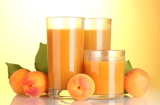 Verres de jus d'abricot sur jaune