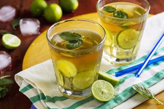 Verres de jus d'été rafraîchissant avec des tranches de citron vert et deux pailles bleues