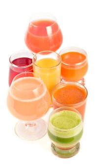 Verres avec jus de fruits et légumes biologiques frais isolés sur blanc.