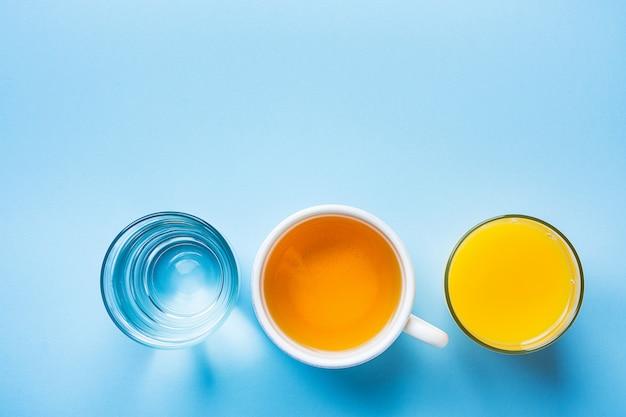 Verres de jus d'orange et d'eau sur fond bleu clair.