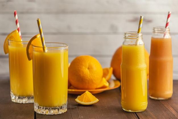 Verres de jus d'orange frais sur bois clair. vue de côté.