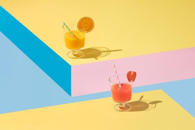 Verres de jus d'orange et de fraise avec des morceaux de fruits placés sur des formes géométriques jaunes, bleues et roses. disposition isométrique. rectangle