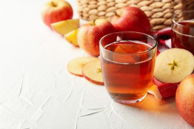 Verres de jus de pomme frais sur blanc