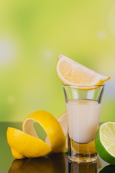 Verres de liqueur de crème au citron vert et citron sur fond vert avec reflet. à court de liqueur de citron. boisson alcoolisée italienne traditionnelle limoncello