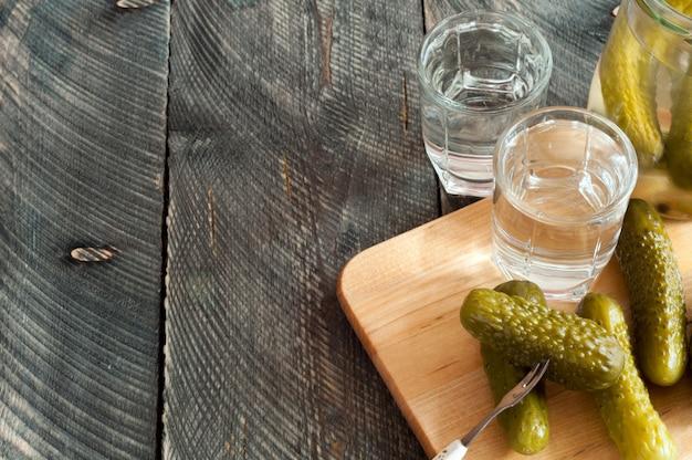 Verres à liqueur avec vodka et concombre mariné sur une fourchette