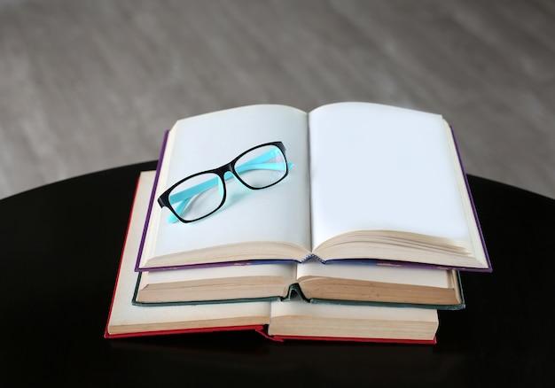 Verres sur livre ouvert sur table en bois.