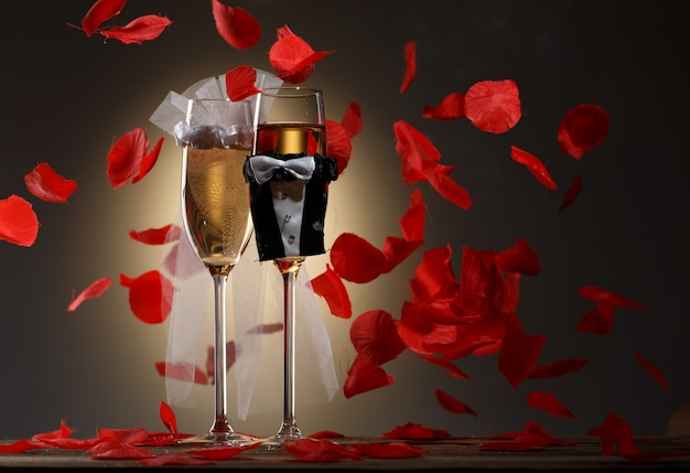 Verres de mariage décorés avec du champagne et un flux de pétales de rose