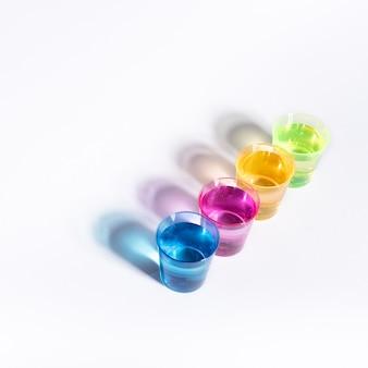 Verres multicolores en plastique avec du liquide sur fond blanc