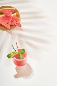 Verres de pastèque margarita cocktail à la menthe et de la glace. boissons rafraîchissantes d'été dans des verres avec des ombres de feuilles tropicales sur fond blanc. concept d'une alimentation saine en été.