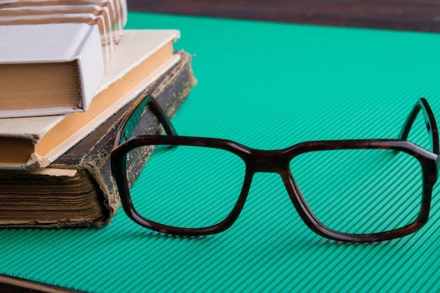 Verres de plan rapproché et pile de vieux livres sur le fond vert