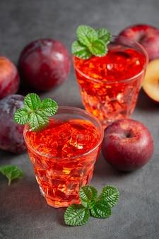 Verres de prune mis sur un sol sombre