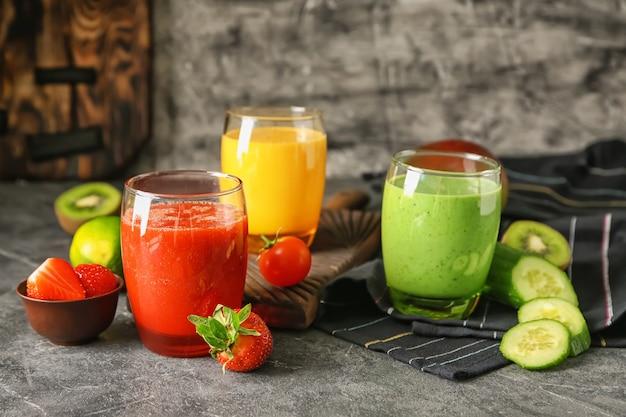 Verres avec des smoothies savoureux frais et des ingrédients sur la table