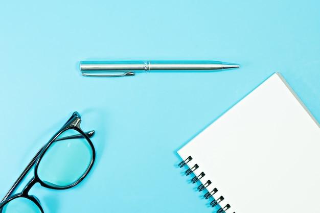 Verres et stylo avec cahier vierge sur fond bleu