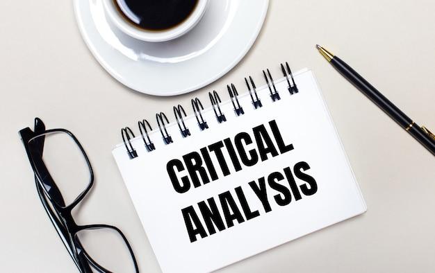 Des verres, une tasse de café blanc, un cahier blanc avec les mots analyse critique et un stylo à bille se trouvent sur une surface claire