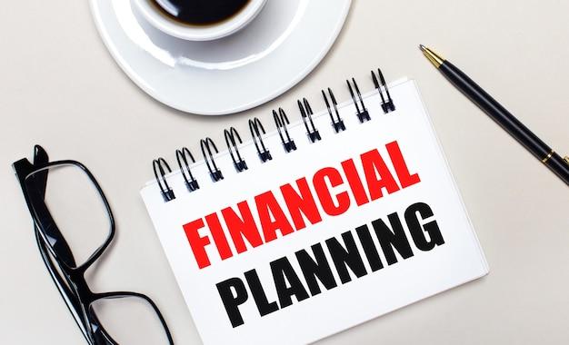Des verres, une tasse de café blanche, un cahier blanc avec les mots financial planning et un stylo à bille se trouvent sur un fond clair. mise à plat. vue d'en-haut.